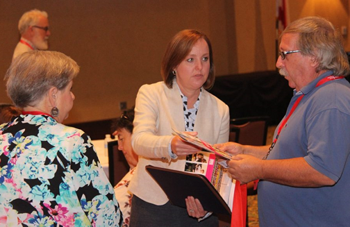 ADRS Commissioner Jane Elizabeth Burdeshaw provides a copy of the ADRS annual report to a conference attendee